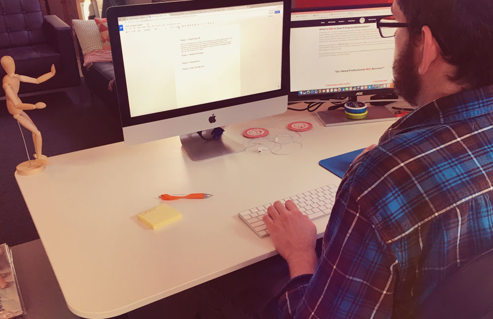 Employee at desk writing blog post for a business